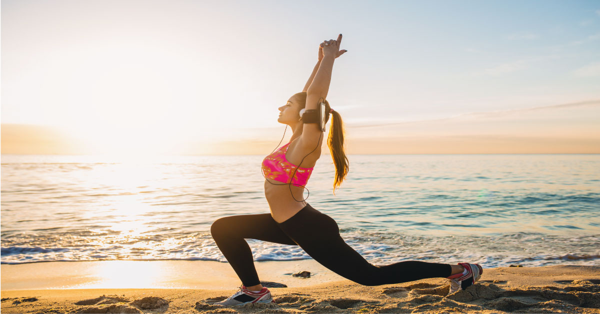 young woman doing workout and exercises in sunrise at beach